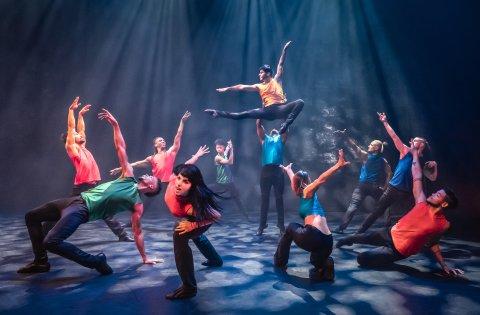 Eine Gruppe Tänzer und Tänzerinnen tanz auf einer Bühne und macht Hebefiguren.