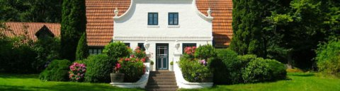 Weißes Haus mit rotem Dach umringt von Bäumen und Wiese