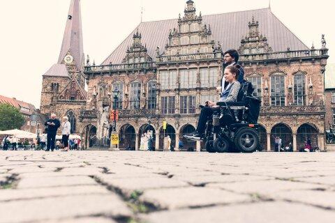 Ein Mann und eine Frau auf dem Marktplatz vor dem Bremer Rathaus. Die Frau sitzt im Rollstuhl.