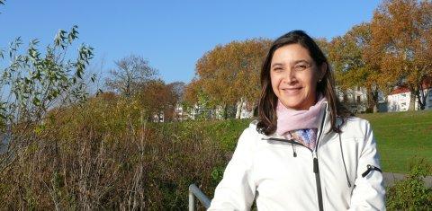 Ana Maria Becker lächelt in die Kamera. Sie steht vor einer großen Treppe.