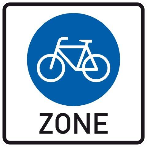 """Ein eckiges Verkehrsschild mit weißem Fahrrad auf blauem Kreis und Beschriftung """"Zone"""" weist den Beginn einer Fahrradzone aus"""