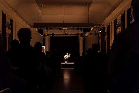 Ein Mann mit einer Gitarre in der Hand sitzt auf der Bühne. Das Scheinwerferlicht leuchtet ihn an. Vor ihm im dunkeln sitzt das Publikum.