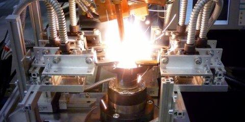 Ein Laser schweisst etwas auf einem Träger aus Metall