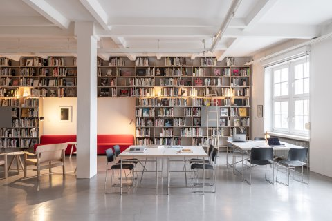 Abgebildet ist eine Bibliothek mit vielen Büchern.