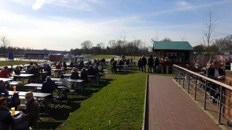 Menschen sitzen draußen an Tischen und trinken Bier.