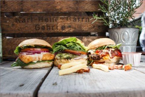 Drei verschiedene Burger auf einem Holztisch.