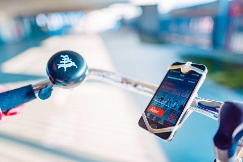 Das Bild zeigt einen Fahrradlenker an dem ein Smartphone und eine Fahrradklingel mit den Bremer Stadtmusikanten befestigt sind