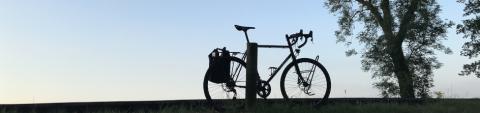 Ein Fahrrad steht auf einem Hügel abgestellt neben einem Baum vor blauem Himmel