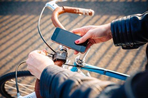 Handy wird am Fahrradlenker befestigt