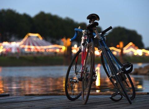Zwei Fahrräder lehnen am Deich aneinander. Breminale im Hintergrund.