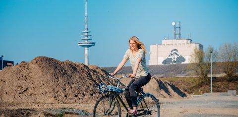 Frau fährt Fahrrad, hinter ihr zu sehen der Bremer Fernsehturm