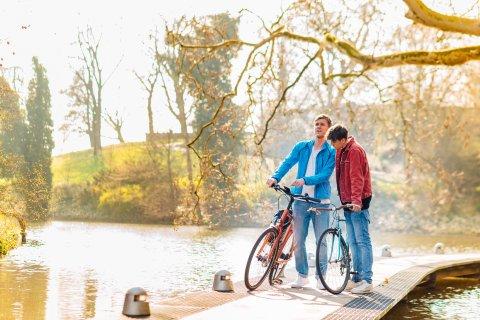 Zwei Männer stehen mit ihren Fahrrädern auf einer Brücke