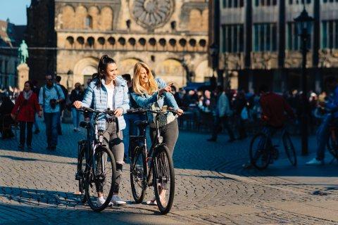 Zwei junge Frauen schieben auf dem Bremer Marktplatz ihre Fahrräder