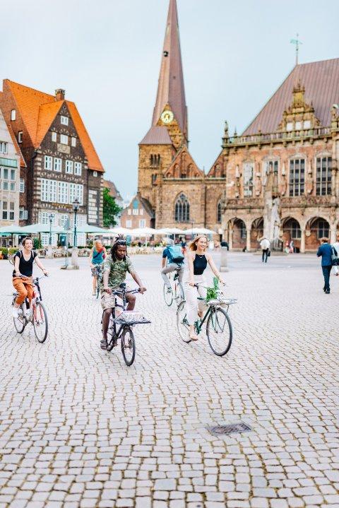 Eine Gruppe von jungen Radfahrerinnen und Radfahrern fährt über den Marktplatz. Im Hintergrund sind das Rathaus und die Liebfrauenkirche zu sehen