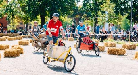 Menschen fahren auf Lastenrädern um die Wette, im Hintergrund Zuschauer