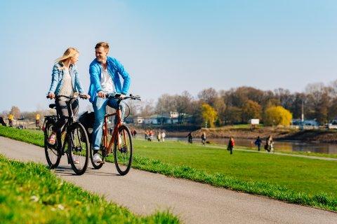 Ein junges Paar fährt Fahrrad am Deich
