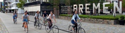 """Junge Menschen auf fahren Fahrrad. Hinter ihnen Häuser und der Schriftzug """"Willkommen in Bremen"""""""