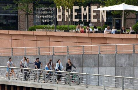 Eine Gruppe Fahrradfahrer vor dem Schriftzug Bremen in der Überseestadt.