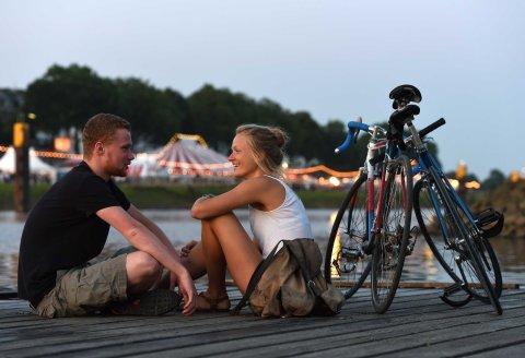 Ein junger Mann und eine junge Frau sitzen zur Abenddämmerung in sommerlicher Kleidung neben ihren Rädern auf einem Steg an der Weser, im Hintergrund die Lichter der Breminale.
