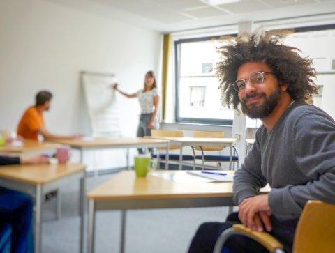 Ein Mann mit wuschelig-lockigem Haar und einer Brille sitz in einem Kursraum und lächelt in die Kamera. Im Hintergrund andere Kursteilnehmende und eine Lehrerin.