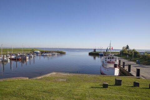 Der Himmel über einem kleinen Hafenbecken ist blau. Es liegen kleine, weiße Schiffe im Hafen.