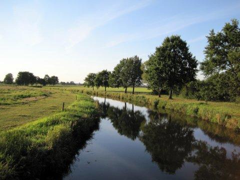 Wasserlauf, von Wiesen umgeben