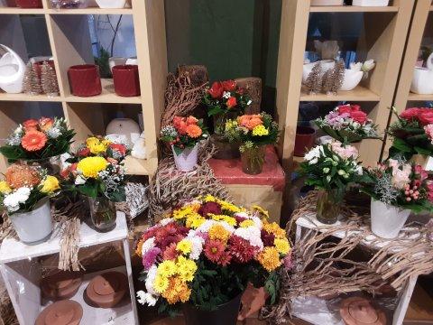 Ein Laden von innen. Verschiedene Blumensträuße stehen auf einer Anrichte. Dahinter stehen bunte Blumentöpfe im Regal.