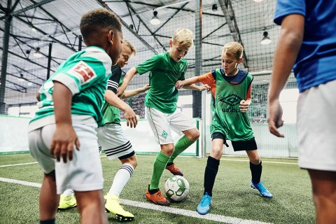 Vier Jungen spielen Fußball in einer Halle. Die Kinder tragen Werdertrikots.