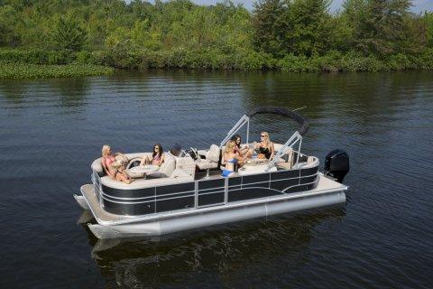 Eine Gruppe von Frauen sitzt bei Sonnenschein in einem Boot.
