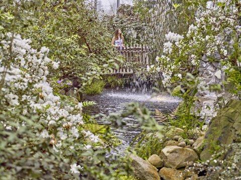Ein Mädchen steht auf einer Brücke in einem Gewächshaus, umgeben von grünen Pflanzen mit Blüten.