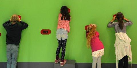 An einer knallgrünen Wand sind Apparaturen angebracht, durch die vier Kinder etwas beobachten