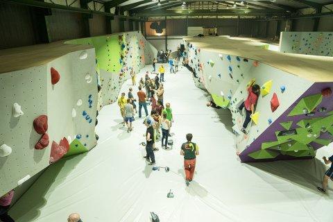 Blick von oben auf einen Gang, an dessen Seite Kletterwände aufgestellt sind. Im Gang stehen viele Personen. Vorne rechts klettert eine Person an der Kletterwand.