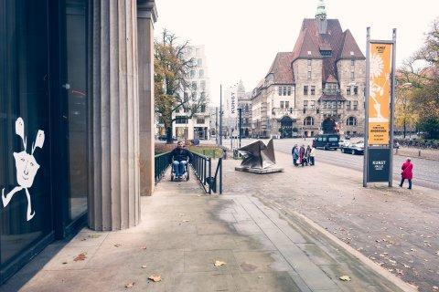 Ein Mann im Rollstuhl fährt die Rampe vor der Kunsthalle Bremen herauf.