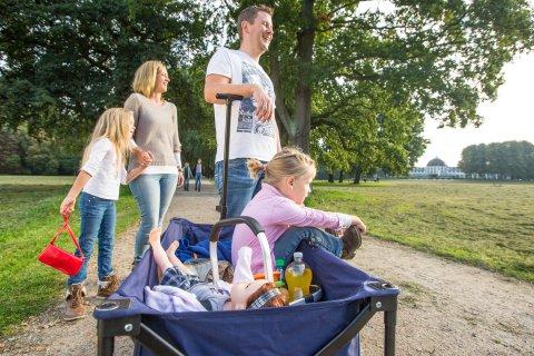 Eine junge Familie mit Bollerwagen im Park