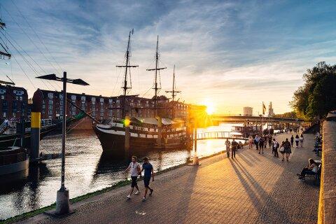 Das Pfannkuchenschiff Admiral Nelson und schlendernde Menschen an der abendlichen Weserpromenade Schlachte