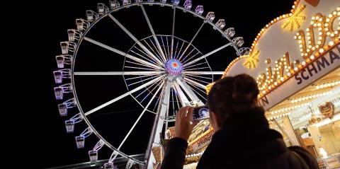 Eine Frau macht mit ihrem Smartphone ein Foto von einem beleuchteten Riesenrad auf dem Jahrmarkt.