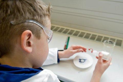Kind führt im Kittel und Schutzbrille ein Experiment durch