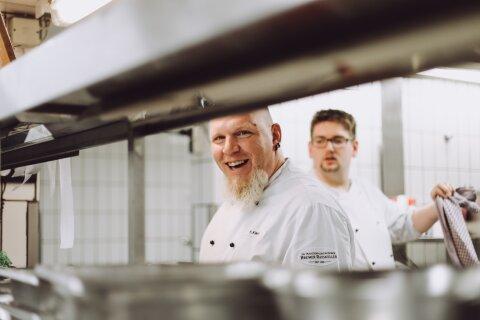 Ein Koch in der Küche des Bremer Ratskeller lächelt in Richtung Kamera, im Hintergrund einer seiner Kollegen.