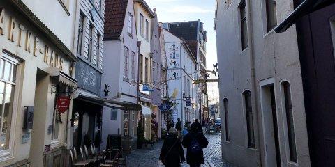 Eine schmale Gasse, die von alten Fachwerkhäusern gesäumt ist. Hier befinden sich Cafés und Menschen gehen Sspazieren.