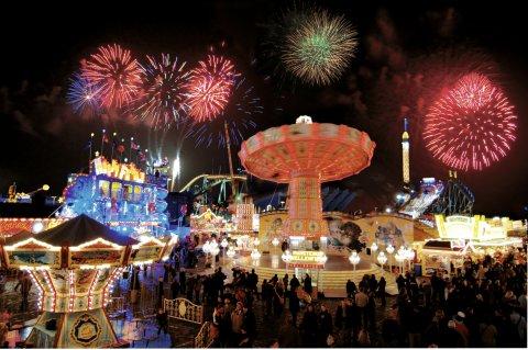 Beleuchtete Buden und Fahrgeschäfte auf dem abendlichen Bremer Freimarkt, darüber ein Feuerwerk