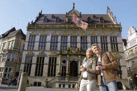 Eine Frau und ein Mann stehen vor einem Gebäude, an dem eine rote, weiße Fahne weht.