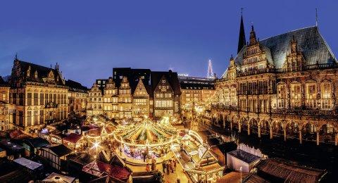 Beleuchtete Buden und ein Karussell auf dem Bremer Marktplatz zur Weihnachtszeit.