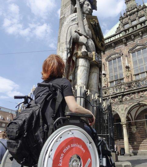 Eine Person sitzt in einem Rollstuhl und guckt sich eine steinerne Statue an.