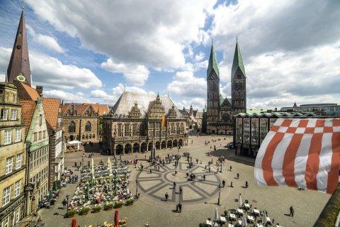 Vogelperspektive auf den Marktplatz. Die Aufnahme zeigt mehrere Gebäude sowie den Dom mit zwei Türmen.