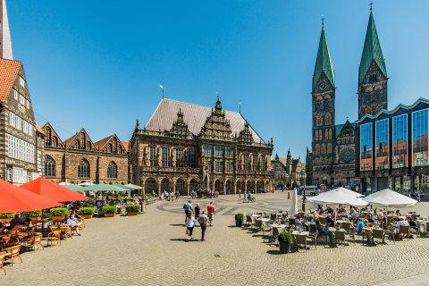 Aufnahme eines Platzes, auf dem Tische, Stühle und Sonnenschirme stehen. Der Platz ist von mehreren Gebäuden umgeben.