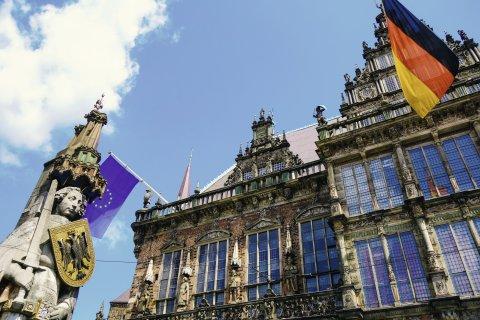 Froschperspektive auf eine steinerne Statue, die ein Schild und ein Schwert hält und auf ein Gebäude, an dem die Flagge Deutschlands und Europas hängt.