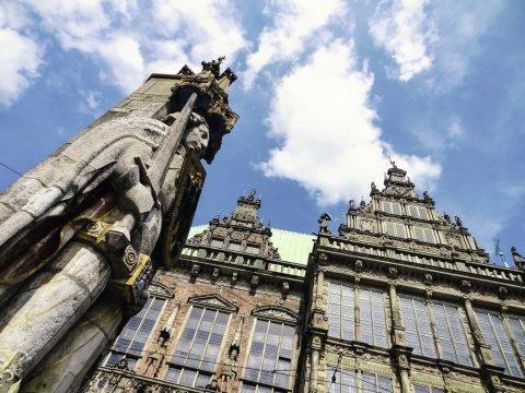 Aufnahme aus der Froschperspektive auf eine steinerne Statue, die ein Schwert und ein Schild hält und auf ein Gebäude mit großen Fensterfronten.