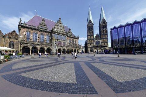 Der Bremer Marktplatz mit dem Rathaus, dem Dom mit zwei Türmen und der Bürgerschaft mit seiner großen Glasfront.
