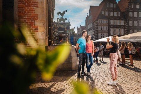 Ein Pärchen steht vor der Bronzestatue der Bremer Stadtmusikanten und lässt sich von einer Frau fotografieren.