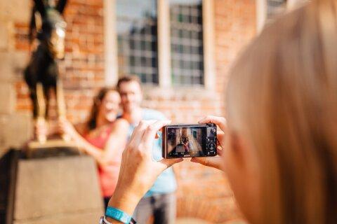 Eine Frau fotografiert eine Frau und einen Mann, welche vor den Bremer Stadtmusikanten posieren.